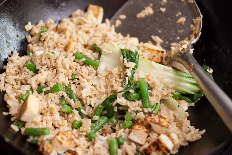 Thai fried rice with tofu beans and pak choi in a wok