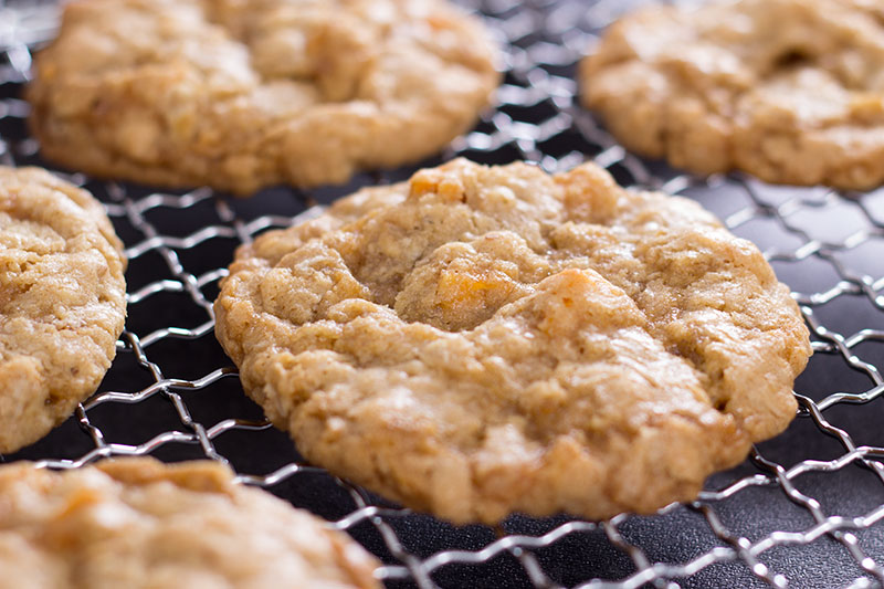 Chewy oat, mango and cardamon spelt cookies on a rack