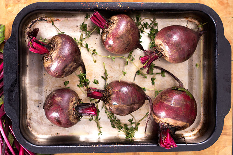 Trimmend beetroot with thyme in roasting tin