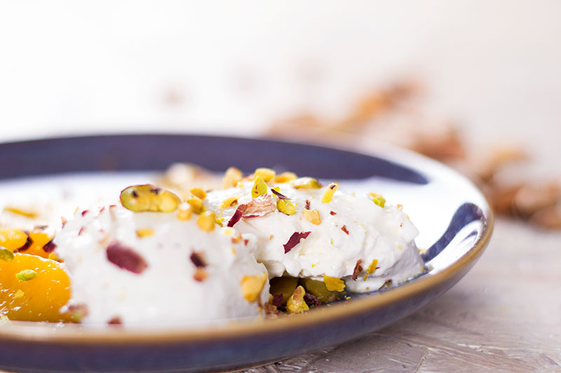 Mango, labneh and pistachio on a plate