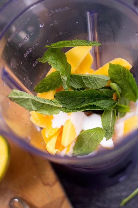 Mango frozen yoghurt with mint in blender
