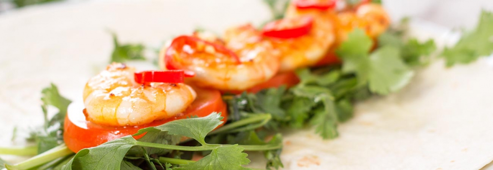 Aromatic prawn and coriander wrap on plate