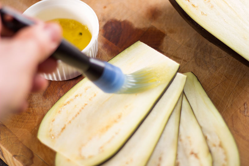 Aubergine slices being brushed with garlic oil