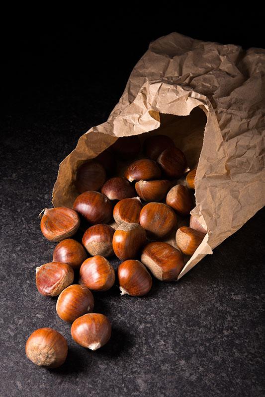 A spilling bag of fresh sweet chestnuts