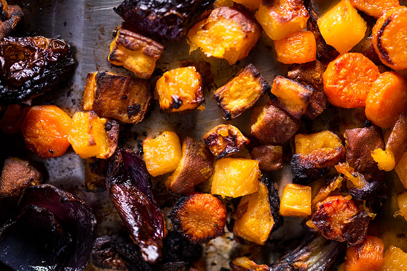 Charred roasted root vegetables in a baking tray