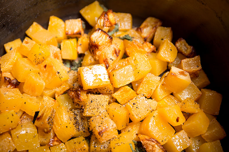 A pile of oven roasted swede with chopped sage