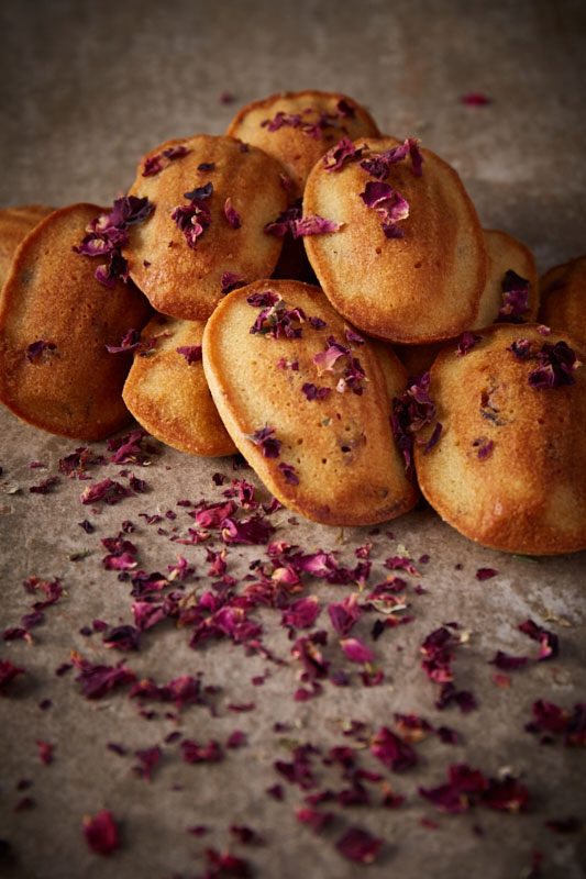 Whimsical spelt madeleines flavoured with fragrant rosewater and decorated with delicate edible rose petals are a delicious afternoon tea time treat as well as being made with no refined sugar, so feature high up on the healthy bake stakes!